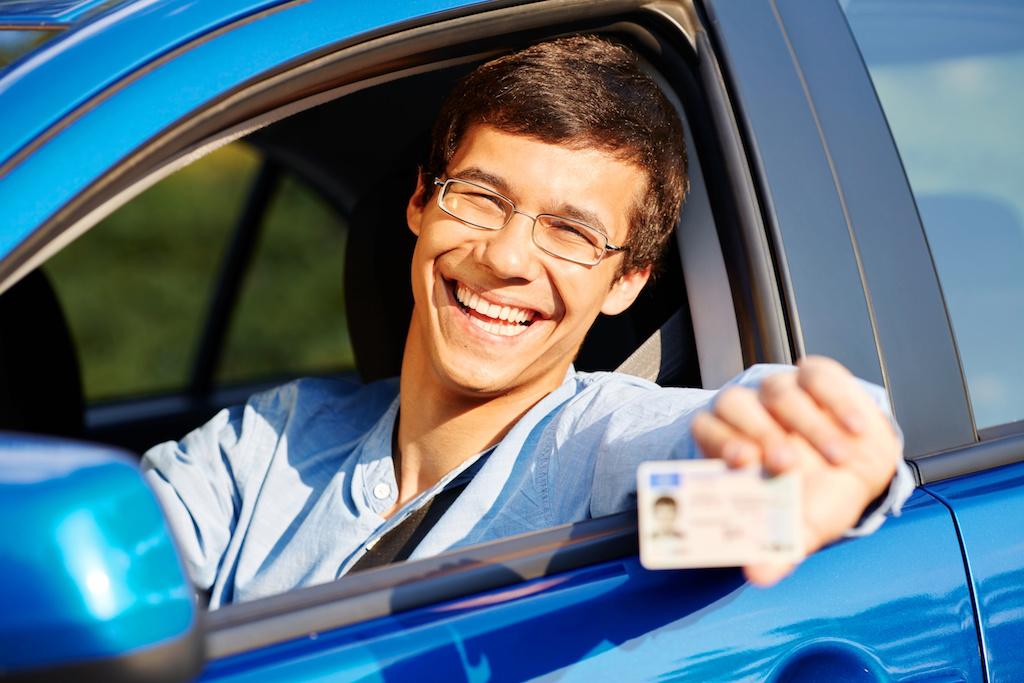 笑顔で免許証を見せる男性